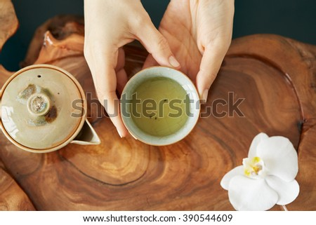 A cup of tea and tea pot on table wood - stock photo