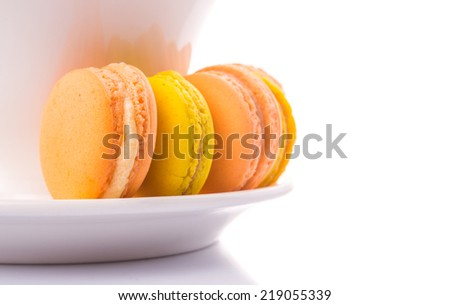 A cup of tea and yellow and orange colored macarons over white background - stock photo