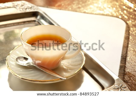a cup of tea in a silver tray, shot on a wooden table - stock photo