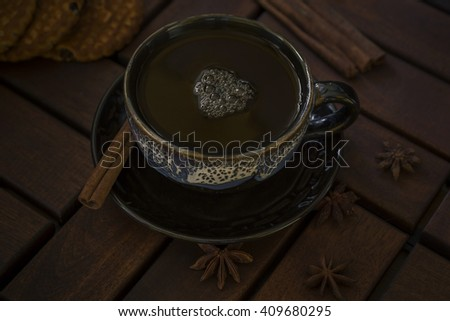 a cup of tea of glazed ceramics. On the saucer cinnamon stick and star anise. Three stars of anise and cookies on a table of dark wood - stock photo
