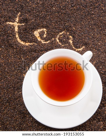 A cup of tea on dried and processed tea leaves with written TEA word - stock photo