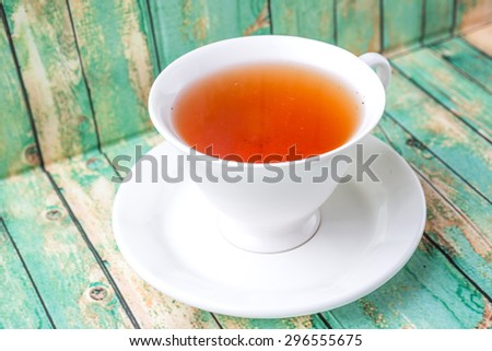 A cup of tea over weathered wooden background