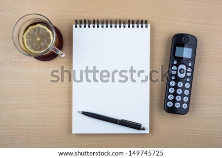 A cup of tea with a lemon, an open notebook, a ballpoint pen and a black phone on wooden texture imitating an office desk. - stock photo