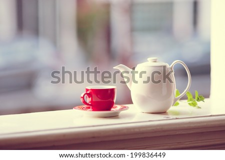 A cup of tea with a teapot. Vintage look. - stock photo