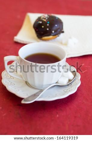 A cup of tea with fresh chocolate sufgniya (donut) - stock photo