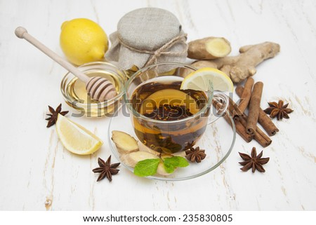 A cup of tea with fresh honey, lemon, ginger and spices on wooden background