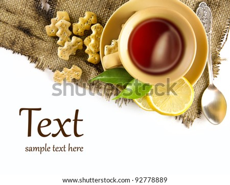A cup of tea with lemon and crackers - stock photo