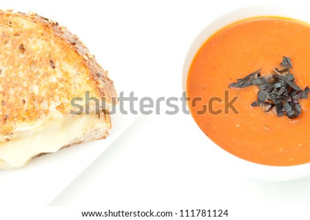 a cup of tomato soup made with fresh heirloom tomatoes and a grilled cheese sandwich made with stone ground whole wheat flour and fresh irish cheddar cheese