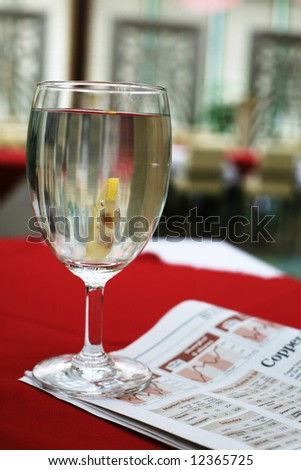 a cup of water over newspaper - stock photo