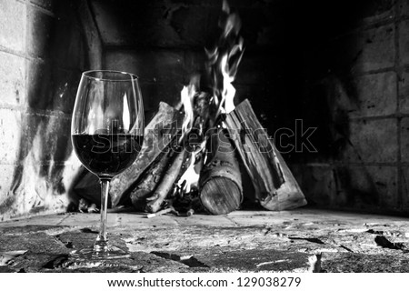 A cup of wine with fire on the background, romantic meal. Love. Write your own message. Photo in black and white. - stock photo