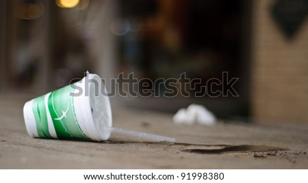A cup tipped over with spilt water - stock photo