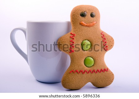 A cup with a gingerbread man stood next to it