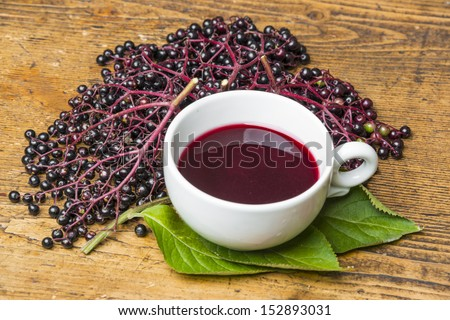 a cup with elder juice on a table - stock photo