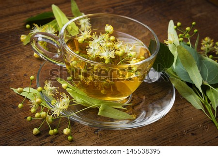 a cup with linden tea and flowers on wooden table - stock photo