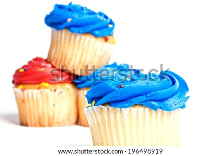 A cupcake with blue frosting and sprinkles with other cupcakes in the background. - stock photo