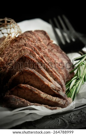 A curated image of perfectly cooked prime topside roast beef, sliced and ready to eat against a dark, rustic background with copy space. Concept image for a restaurant Sunday lunch menu cover design. - stock photo