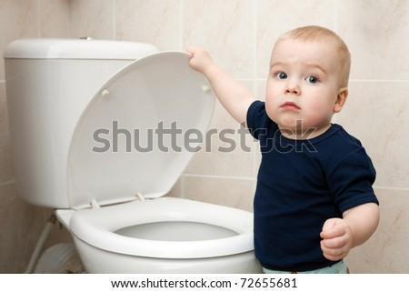 a curious little boy looks in the toilet - stock photo