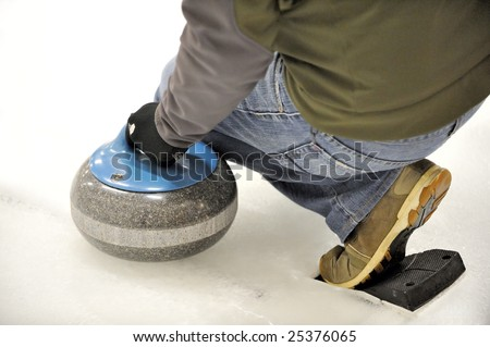 A curler prepares to launch the granite rock, with his foot braced by the hack. - stock photo