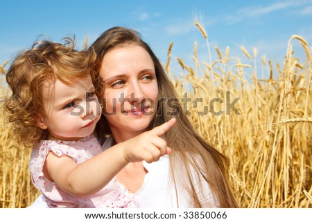 A curly girl showing something to her mother - stock photo
