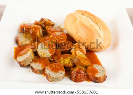 a curry sausage with roll on a plate