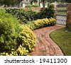 A curved brick path graced with beautiful yellow mums and a garden gate held up with a brick wall. - stock photo