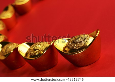 A curved row of traditional chinese gold ingots on a red background - stock photo