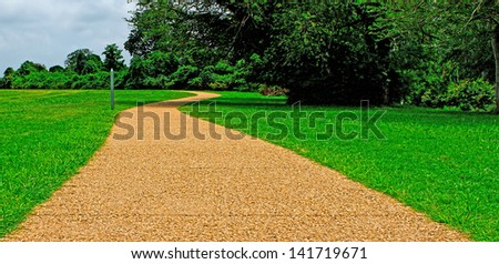 A curved stone walkway along side of the woods on an overcast day in yorktown Virginia leading away to the beach - stock photo