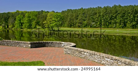 A curved stone wall overlooking a reflecting lake. - stock photo