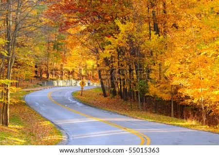A curving autumn road with a hiker in the far distance - stock photo