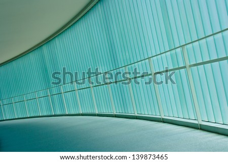 A curving corridor is illuminated with soft blue light through a frosted glass wall. - stock photo