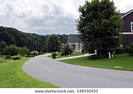 A curving road through a modern neighborhood. - stock photo