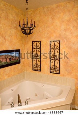 a custom faux finished wall surronds a luxury jetted tub (picture on the wall shot by me) - stock photo