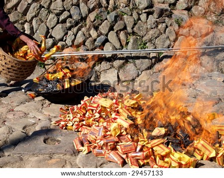 A custom in Chinese. People burn the  Ghost Money and paper materials to  honor the ancestor in festival so that their ancestor still can rich in heaven or hill. - stock photo