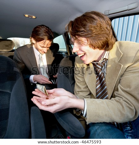 A customer in the backseat giving a tip to the cabby after having reached the destination - stock photo