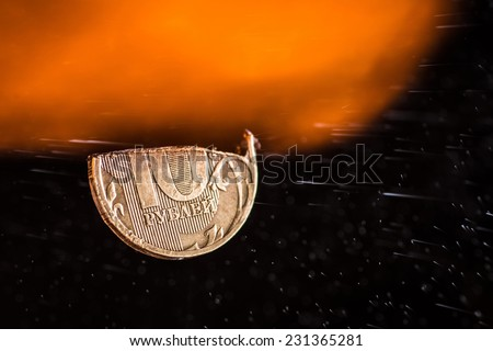 A cut ten rubles half-coin in fire and dust, concept of inflation and financial crisis in Russian Federation. - stock photo