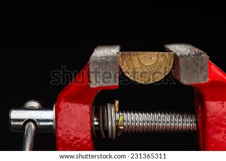 A cut ten rubles half-coin squeezed in a metal vise jaws, concept of financial crisis and currency devaluation in Russian Federation. - stock photo
