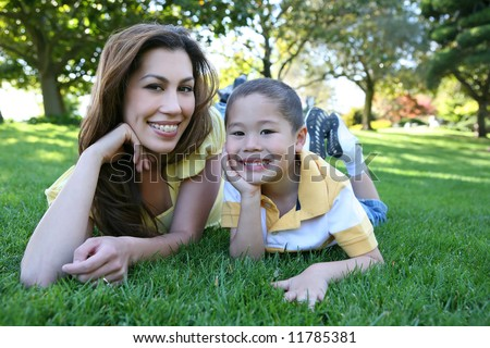 A cute and pretty mother and son laying on grass in the park