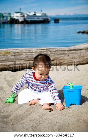 A cute asian boy playing with sand on the beach - stock photo