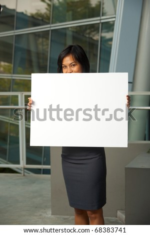 A cute Asian business professional in gray skirt hides face behind a blank sign outside in front of a modern office building.   Custom text copy insert. 20s female Asian Thai model of Chinese descent
