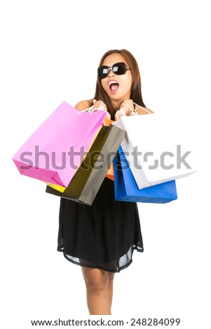 A cute Asian girl shopper in black dress, stylish sunglasses, playfully mouthing words with open mouth, holds raised department store shopping bags in front. Thai national of Chinese origin. Vertical