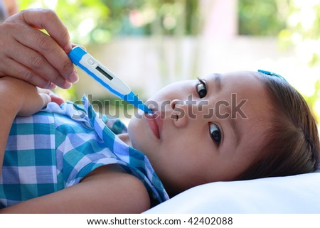 a cute asian girl with a fever and thermometer - stock photo