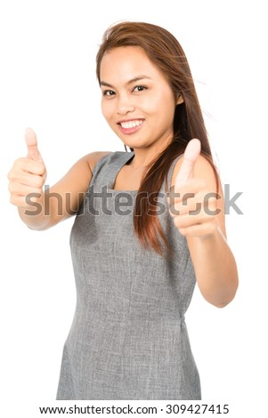 A cute Asian girl with light brown hair in gray sleeveless dress enthusiastic in approving with two thumbs up giving validation, recognition, blessing or compliment. Thai national of Chinese origin V - stock photo