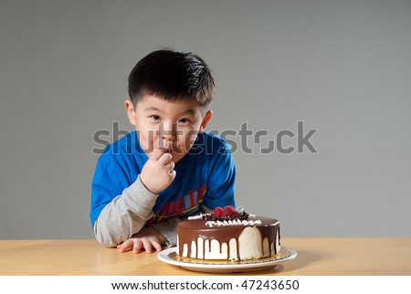 A cute Asian kid posing with a birthday cake, nibbling at the cake.