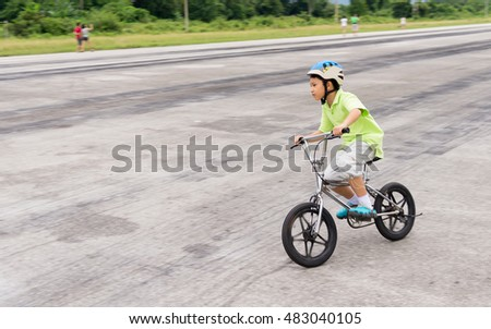 A cute Asian kid riding a bicycle with a helmet on.