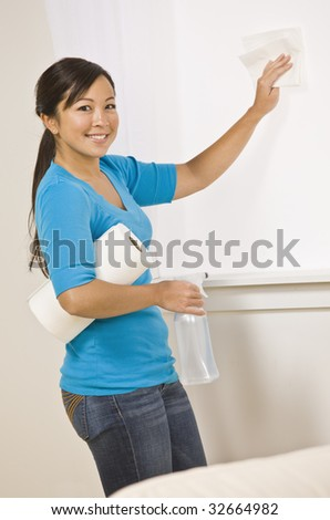 A cute asian woman cleaning in her home.  She is smiling at the camera and is using a roll of paper towels.  Vertically framed shot. - stock photo