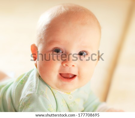 A cute baby girl in fairy wings laughs while looking up at the camera. - stock photo