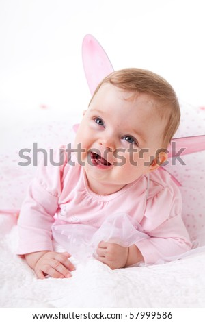 A cute baby girl in fairy wings laughs while looking up at the camera. Vertical shot. - stock photo
