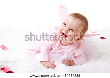 A cute baby girl in fairy wings laughs while lying on the ground covered in flower petals.  Vertical shot. - stock photo