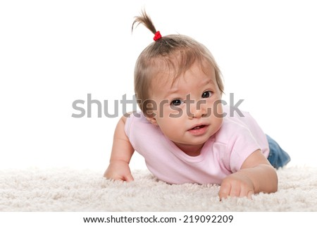 A cute baby girl is lying on the white carpet