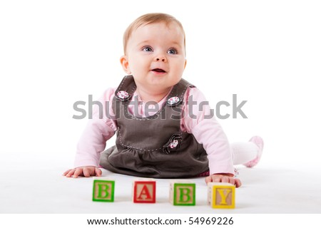 A cute baby girl is posing behind a set of children's blocks that spell out BABY.  Horizontal shot. - stock photo